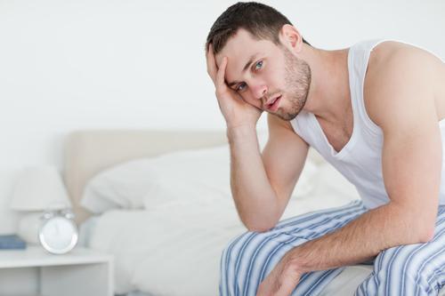 мужчина сидит на кровати и держится за голову